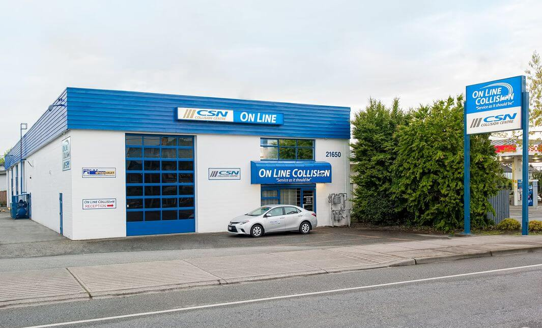 On Line Colision auto body repar shop front during the day. One large blue garage bay door and a entrance for customers.