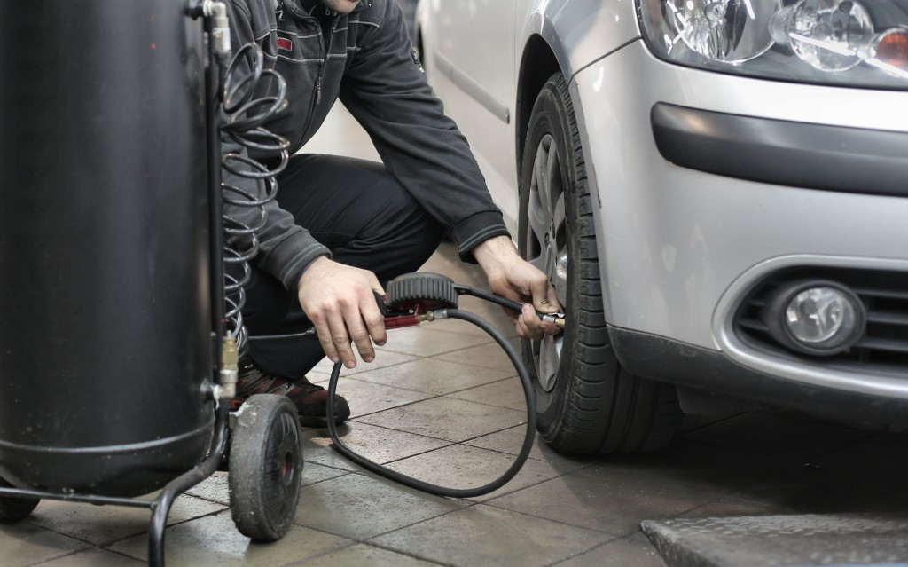 person inflating tire from car